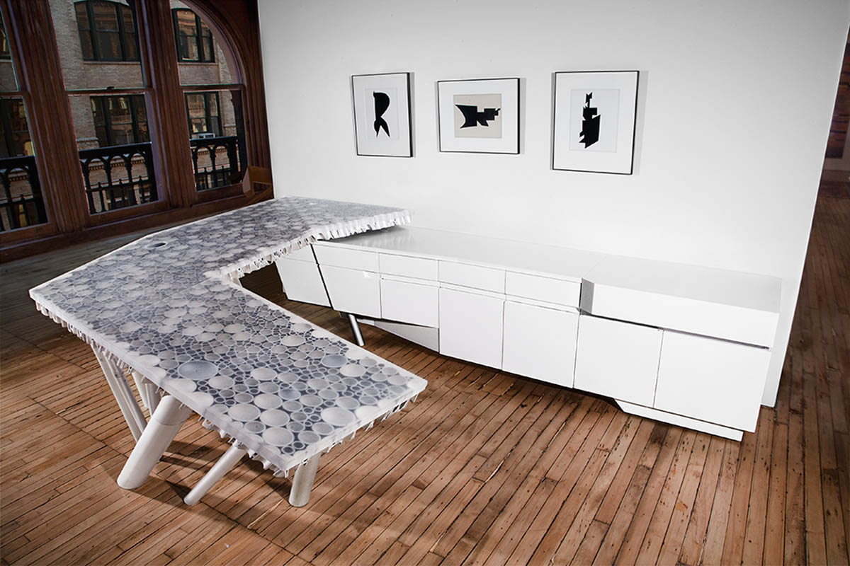 "Located within an NYC loft, this furniture intervention included custom casework and a work surface that appears and disappears as one walks around it. This phenomenon was achieved by the 3"" thick table top compose of cast polyurethane resin and a series of aluminum tube in 5 diameters that are welded to form sections with various angles to allow one to see through certain section depending on the particular viewing point. A series of tubes extend down to become the supports of the table blurring the line between vertical support and horizontal span.image by mathew baum"
