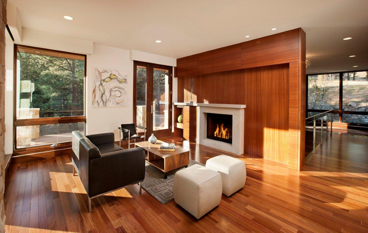 A high-paneled fireplace and divider helps bring out the warmth in this elegant  contemporary living room.