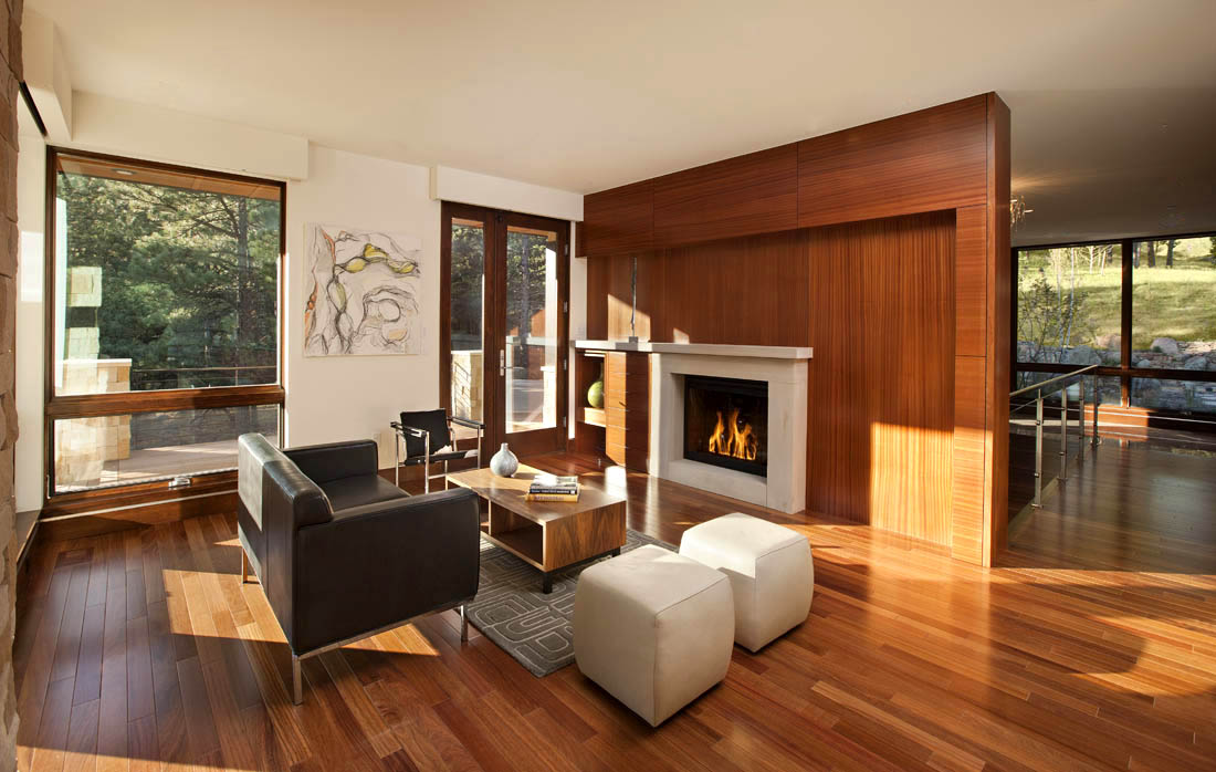 A high-paneled fireplace divider helps bring out the warmth in this warm contemporary living room.