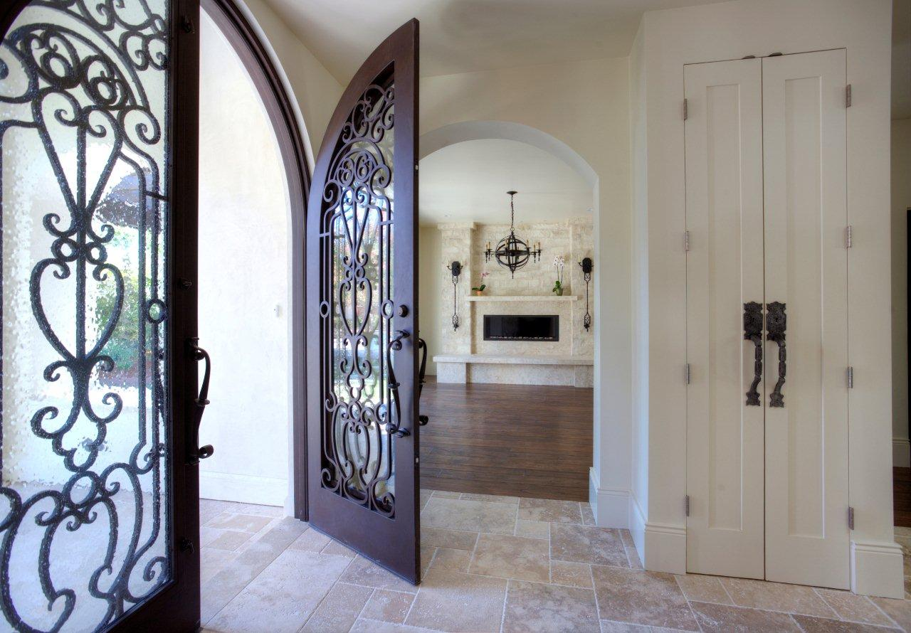 A custom Spanish entrance with specially designed, grand doors and elegant, cool flooring.
