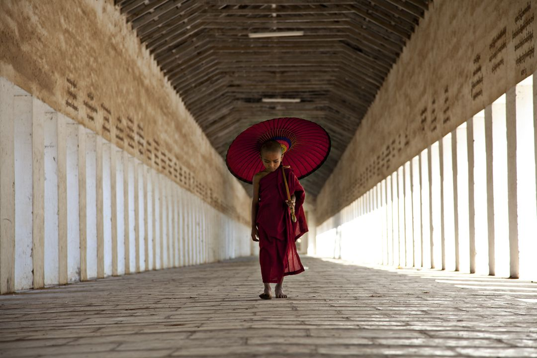 I spotted this young monk as he was walking to his monastery. I loved the expression on his face and his parasol resting on his shoulder.Mandalay, Burma