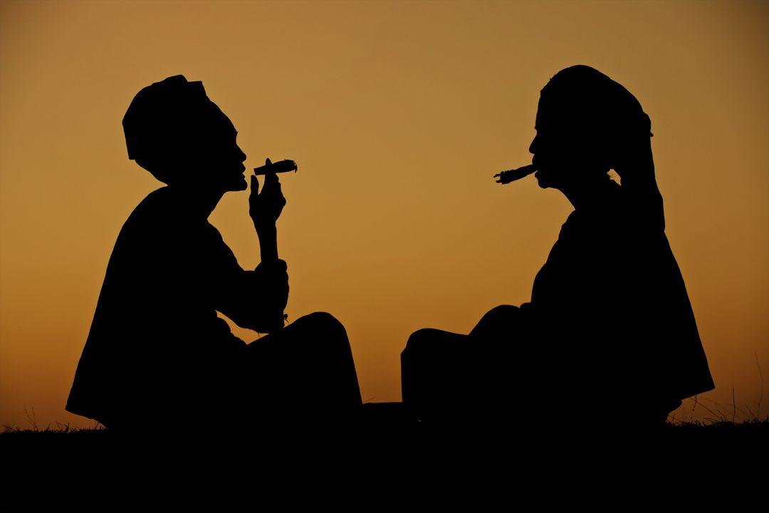 Women smoking on a hill after sunset.Bagan, Burma
