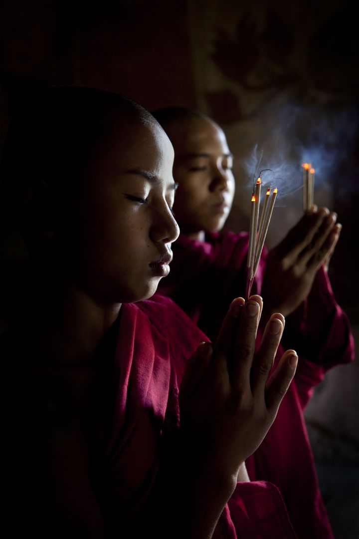 Young monks hold incense as they pray.Minnanthu - Bagan, Burma