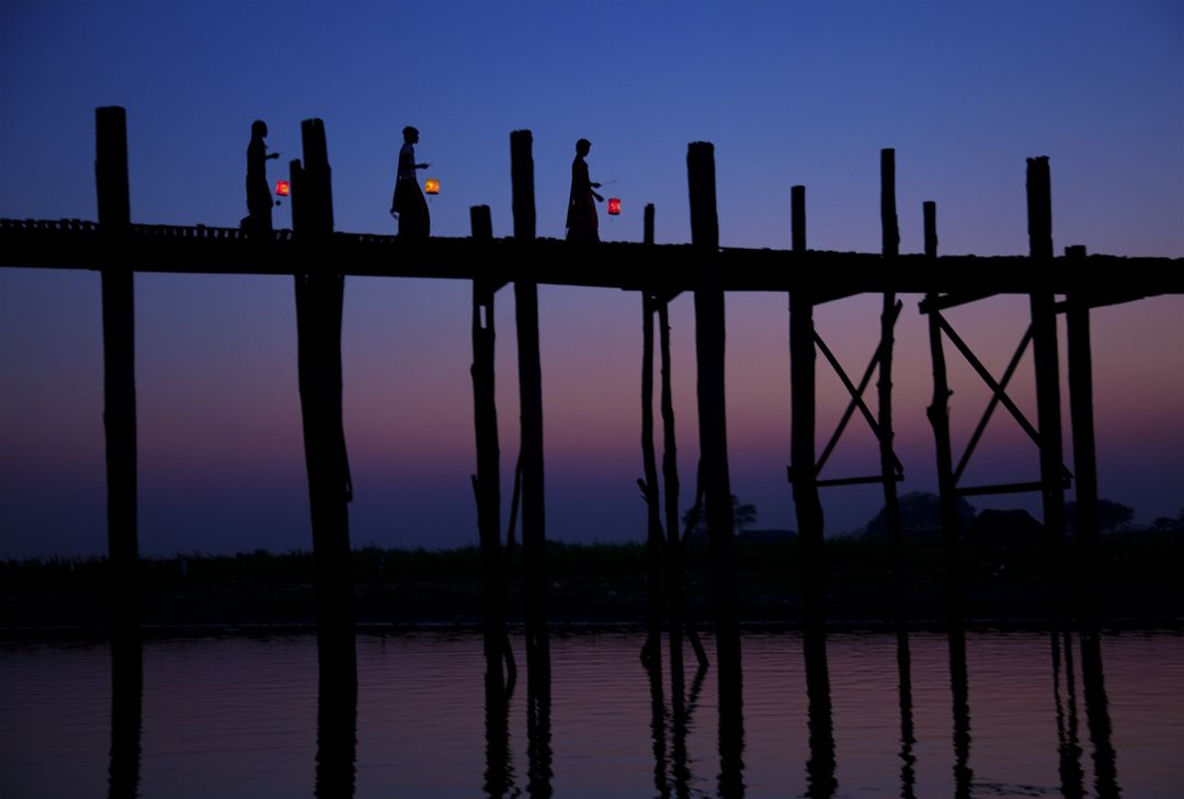 Women crossing the U Bein Bridge at Sunset. The bridge spans 1.2 km across the Taungthaman Lake.Taungthaman Lake - Mandalay, Burma
