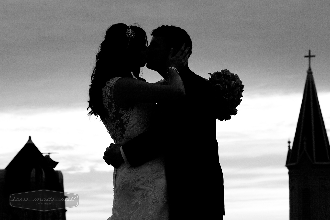 Newlyweds kiss is captured as a silhouette with church in background