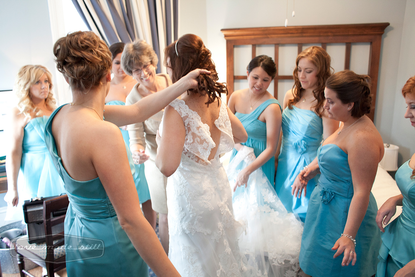 The reaction of the bridesmaids as the bride puts on dress