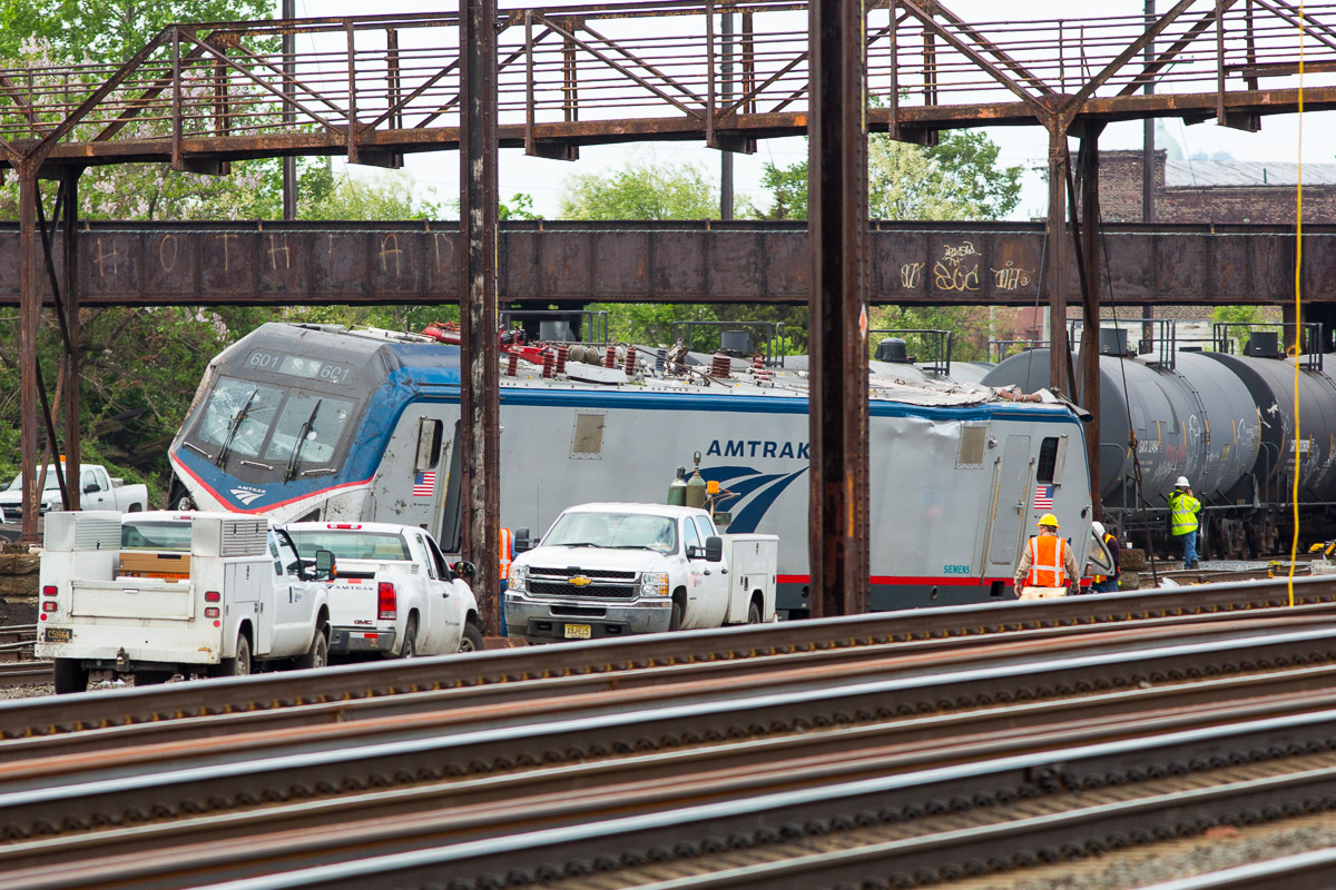 Emergency workers inspect the wreckage of an Amtrak train  derailment in Philadelphia that killed eight people and injured more than 200.