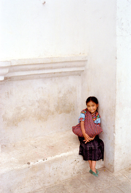 A young girl sits in front of the main church in San Jorge de la Laguna, Guatemala.