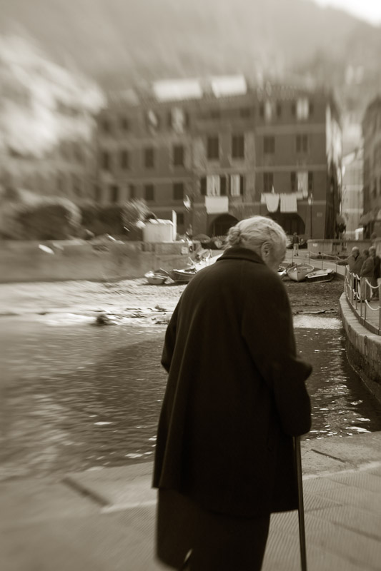 An old woman strolls along the harbor of Vernazza, the northernmost town in Cinque Terre in Liguria, Italy.