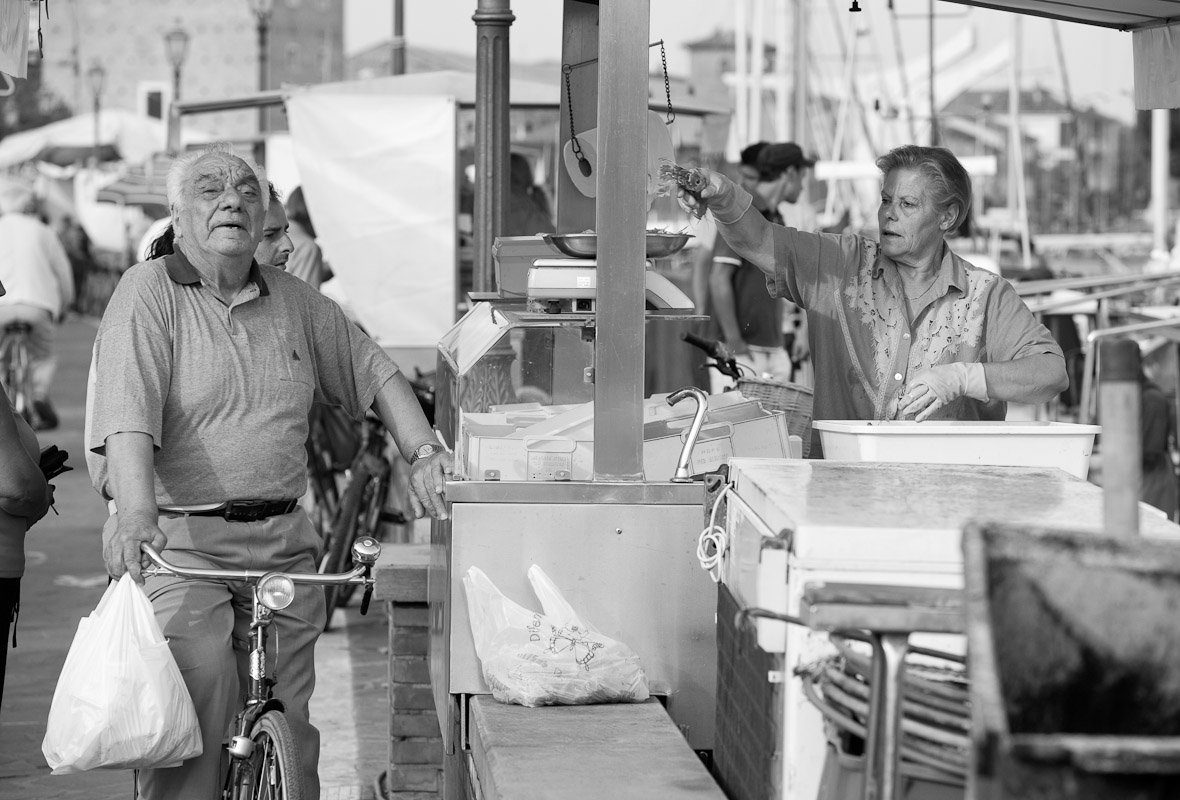 A man shops at a seafood stall in the harbor of Cervia in Emilia Romagna.