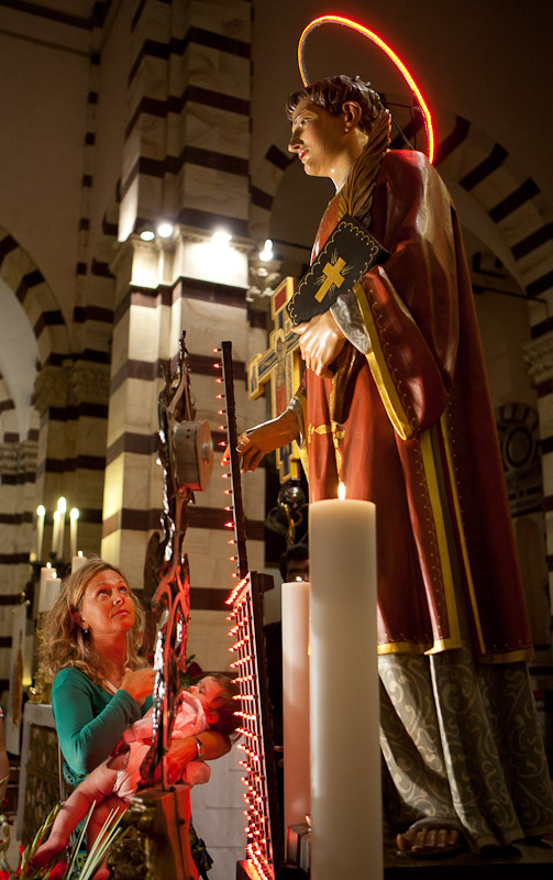A woman prays at the feet of San Lorenzo, the patron saint of Grosseto, in the Cathedral of San Lorenzo during the festival in his honor in Grosseto, Tuscany