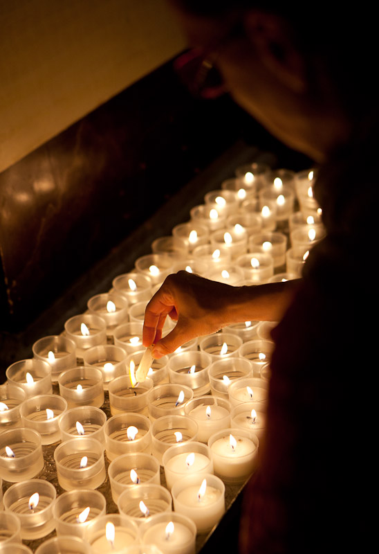 A woman lights a candle in the Cathedral of San Lorenzo during the festival of San Lorenzo, the patron saint of Grosseto, in Grosseto, Tuscany.