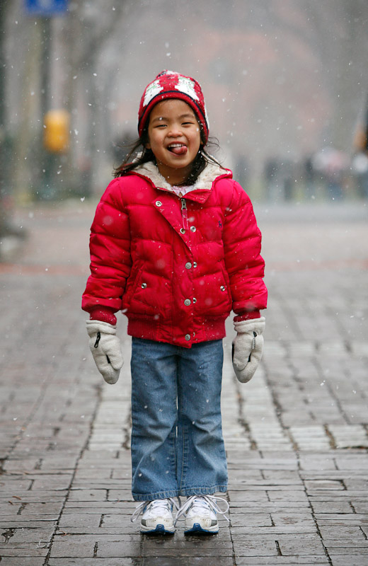 Three-year-old Julia Schenk, seen here on Locust Walk at the University of Pa. in Philadelphia, catches snow flakes on her tongue.