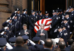 The casket of Philadelphia police sergeant Timothy Simpson, who was killed in the line of duty, is carried by officers out of the Cathedral Basilica of Saints Peter and Paul in Philadelphia following his funeral services.