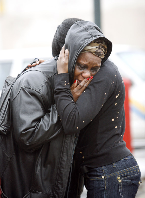 A woman who identifies herself as Olive, a friend of victims killed in a house fire in southwest Philadelphia, sobs while a member of the local Liberian community tries to console her outside the house.