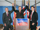 President George Bush Sr., center, raises the arms of Pa. republican senator Arlen Specter, left, and Pa. republican senatorial candidate Rick Santorum during a 2006 campaign rally at a private residence in Gladwyne, Pa.