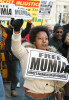 Georgette Kareithi marches through the streets of Philadelphia in support of death-row inmate Mumia Abu-Jamal during a protest marking the 25th anniversary of his incarceration for the murder of police officer Daniel Faulkner.