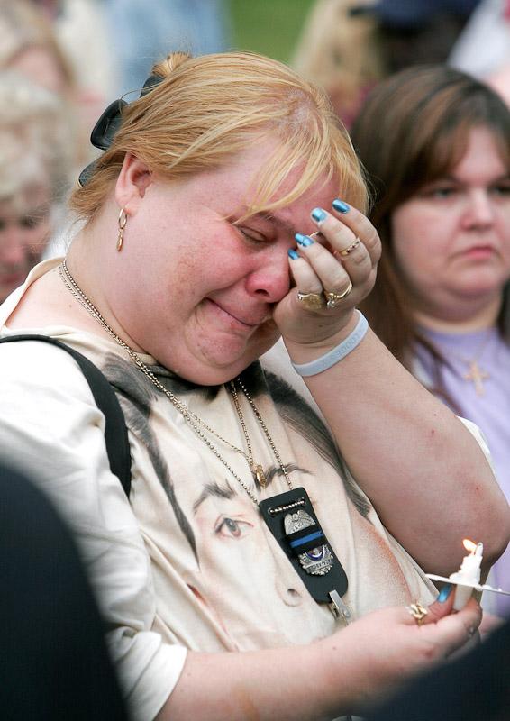 Maureen Boyle, sister of Philadelphia police officer Danny Boyle who was slain in 1991, wipes tears from her face during a vigil for slain police officer Gary Skerski in Philadelphia.