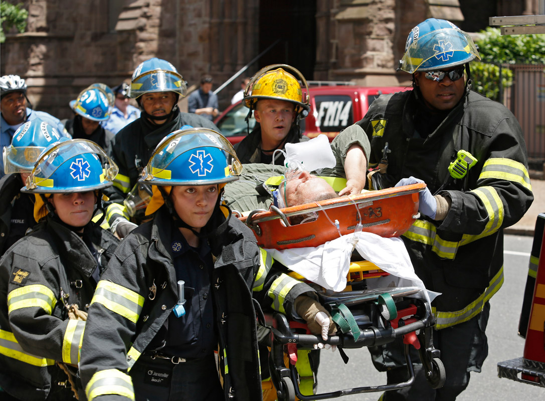 Paramedics rush to an ambulance with a survivor from a 4-storey building that collapsed in center city Philadelphia.