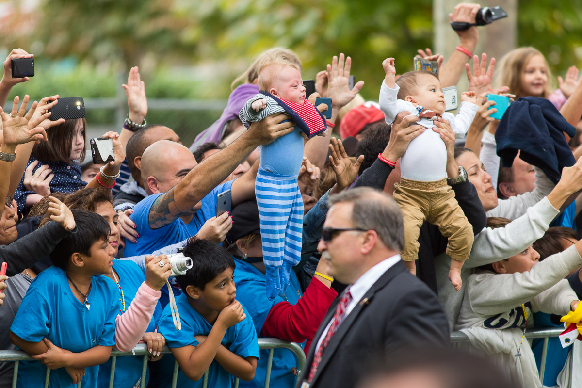 Parents hold their babies up for blessings from Pope Francis as his motorcade passes on the Ben Franklin Parkway in Philadelphia.