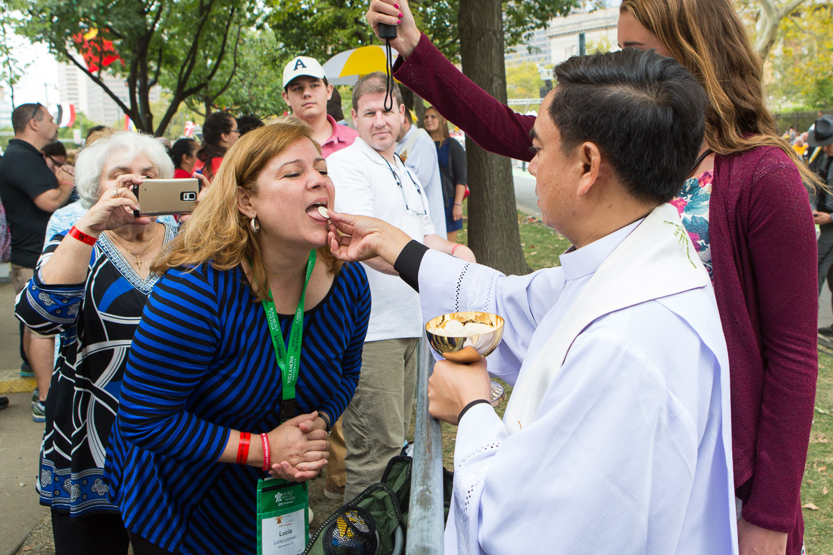 A pilgrim receives communion during mass led by Pope Francis on the Ben Franklin Parkway in Philadelphia.