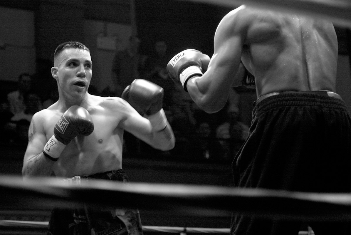 Welterweight Gennaro Pellegrini, Jr., left, prepares for a punch during the first round of his debut, four-round knockout of James Andre Harris at the Blue Horizon in Philadelphia. Pellegrini, a policeman and Army National Guardsman, achieved his goal of winning his first professional fight before being deployed to Iraq, where he was later killed in action.