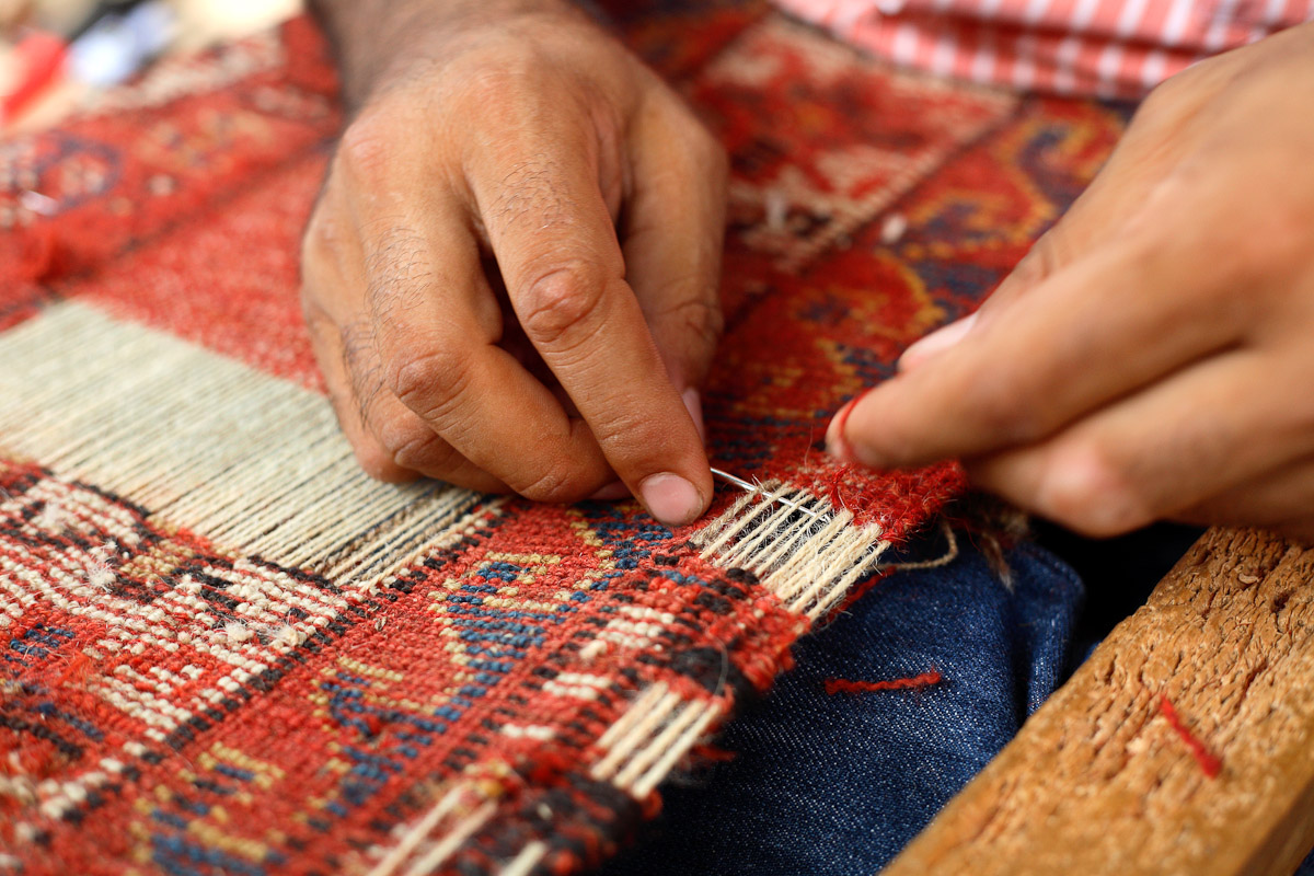 A man repairs a carpet in Istanbul, Turkey.