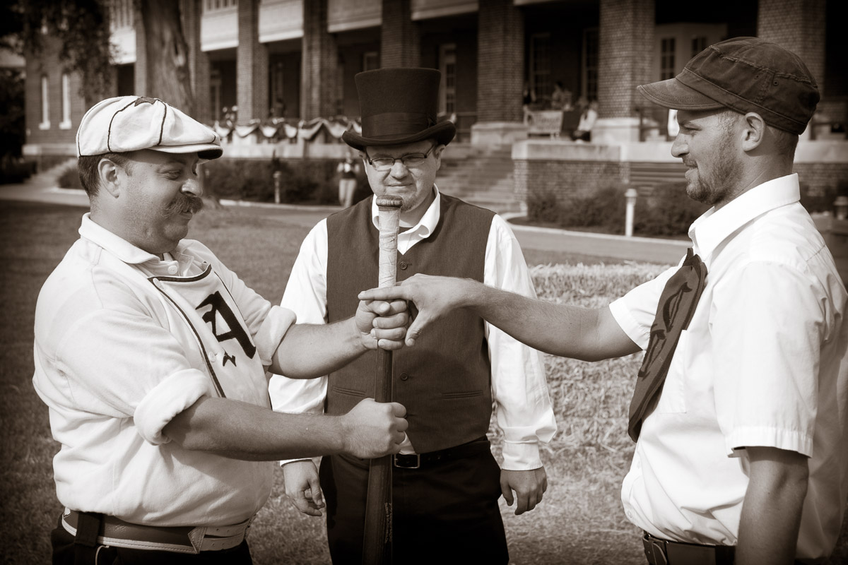 Arbiter Chris {quote}Ring{quote} Goering of the Diamond State Base Ball Club, center, judges the bat toss between Scott {quote}Step Right Up{quote} Alberts of the Athletic Base Ball Club of Philadelphia and the captain of the Cecil Base Ball Club of Chesapeake City, Md. at the Vintage Baseball Festival at the Naval Yards in Philadelphia.