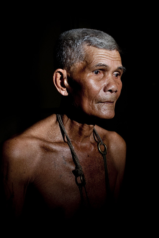 Sa Naam, a Mor Chang, or elephant shaman, poses in Ban Ta Klang. He is one of the last 4 remaining Mor Chang and a spiritual leader of the Kui people.