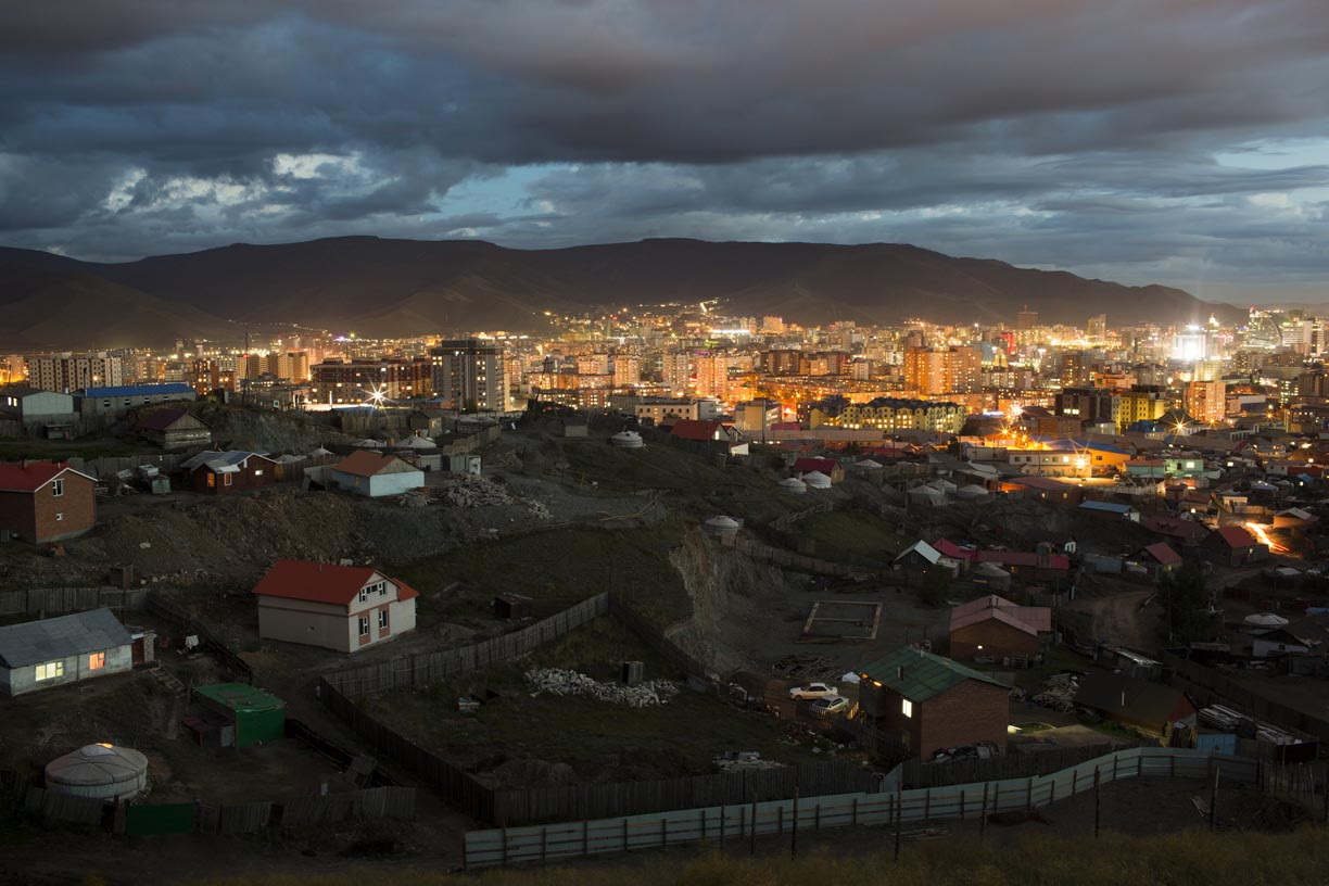 A ger district, bottom, stands near illuminated buildings in Ulaanbaatar, Mongolia.