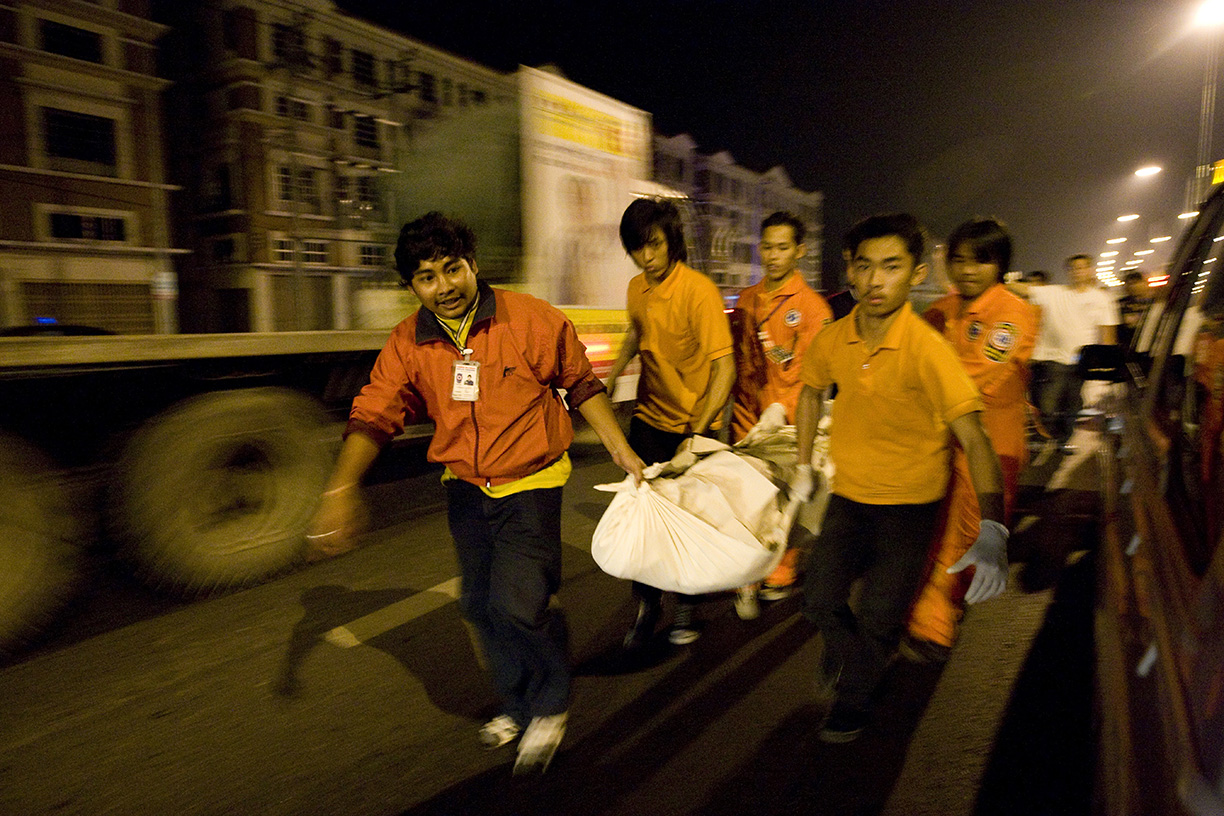 Volunteers carry a dead body to a truck bound for the morgue in Bangkok.