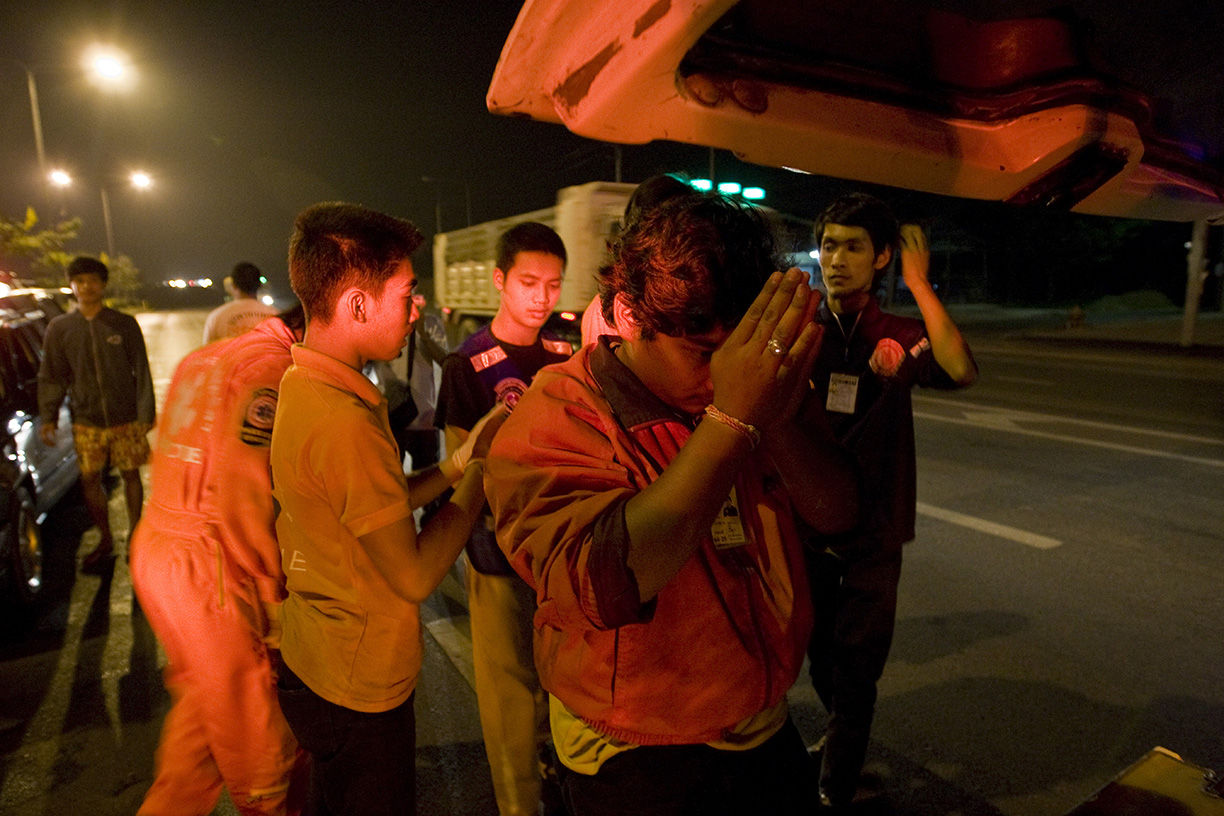 A Por Tek Tung volunteer says a prayer for the dead after loading a body into a vehicle bound for a morgue in Bangkok.