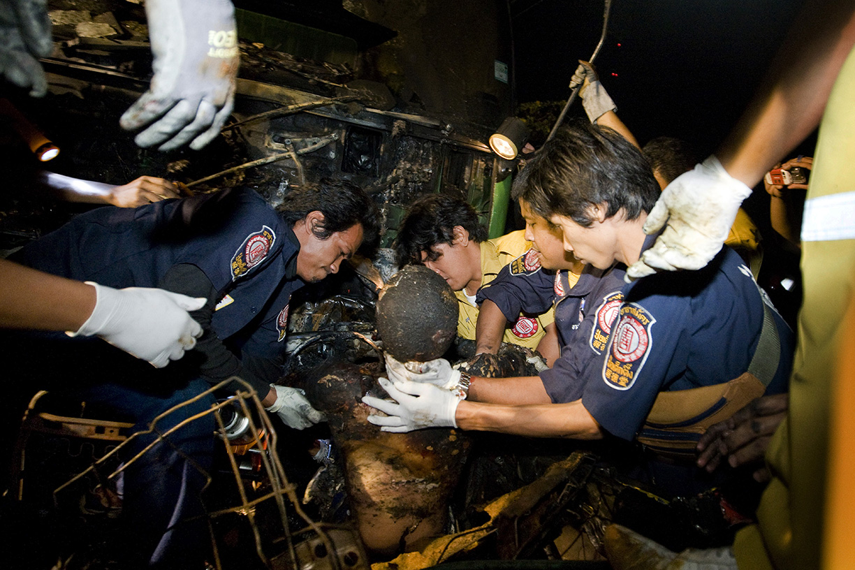 The burnt body of a man involved in a head-on collision is removed from a vehicle in Bangkok.