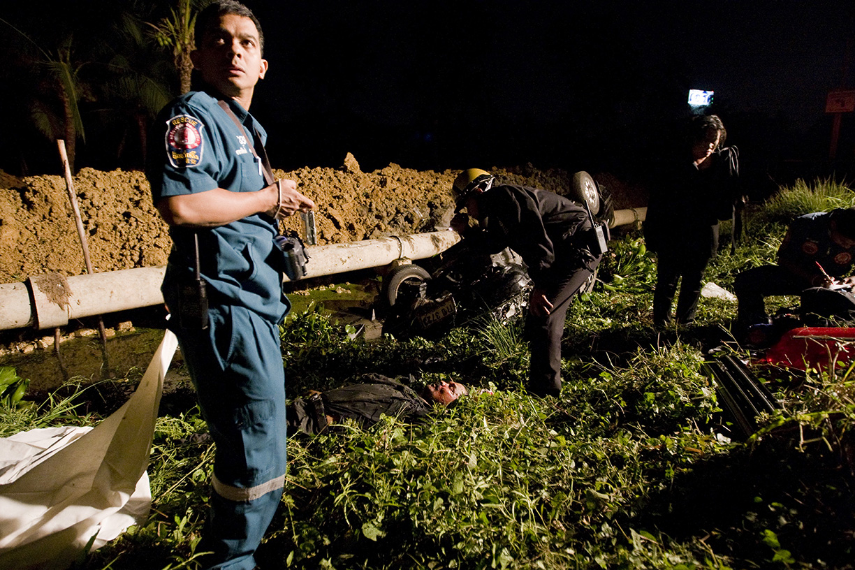 A Por Tek Tung employee prepares to collect the body of a deceased police officer involved in a fatal accident in Bangkok.