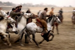A man on a horse carries a goat carcass across a pitch during a buzkashi match in Kabul, Afghanistan.