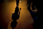 Shadows are cast from mahout, Wan, left, and his pet elephant Boopae as they walk down Sukhumvit road in Bangkok.