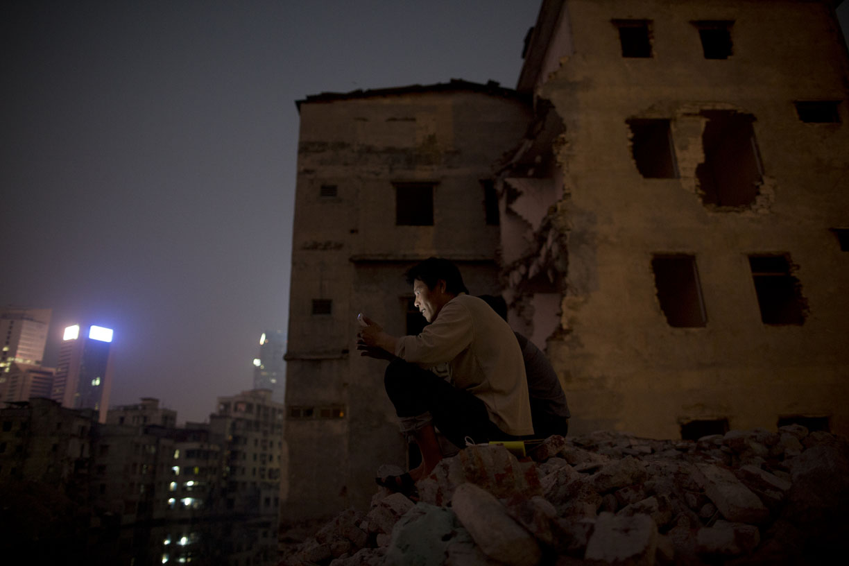 Construction workers watch a movie on a mobile phone near a demolished residential building in Guangzhou, China