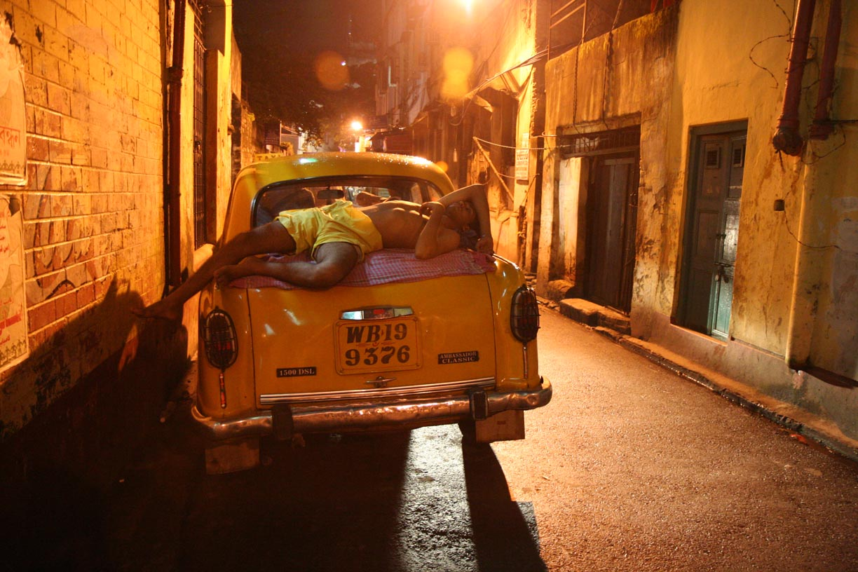 A man sleeps on a taxi in Kolkata, India.