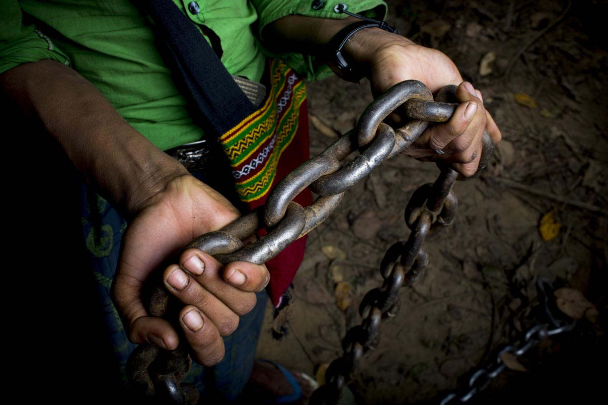 An oozie, or mahout, holds a chain used to pull logs in the Yoma mountain range.