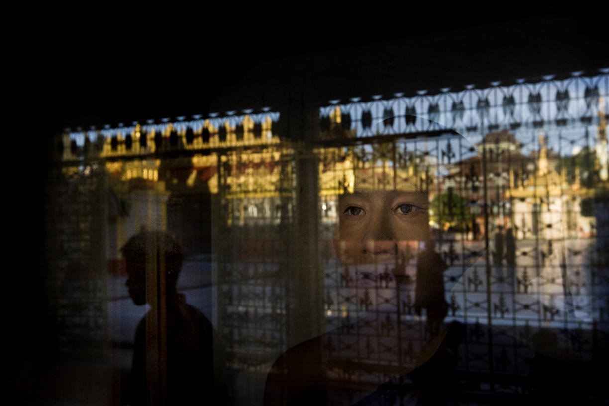 An image of the Buddha is seen behind a glass case at Botataung Paya.