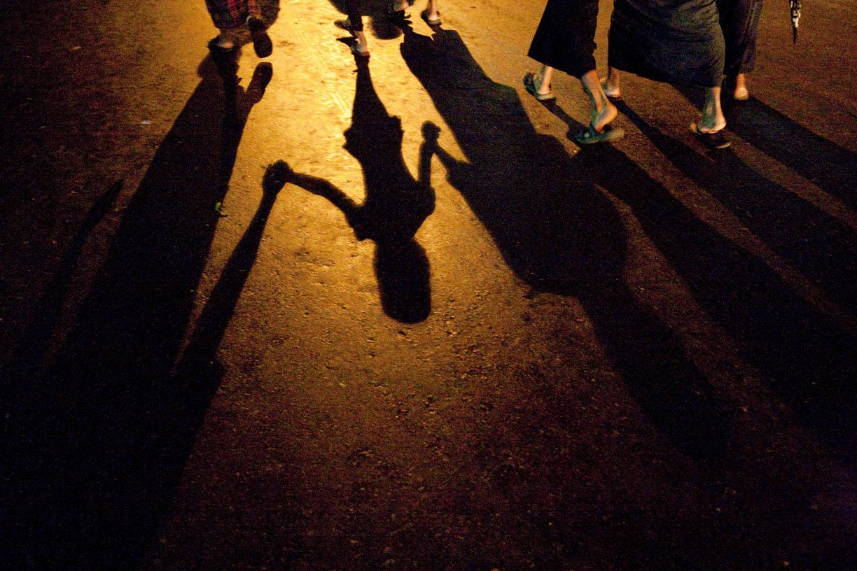 Pedestrian's shadows are cast on a street.