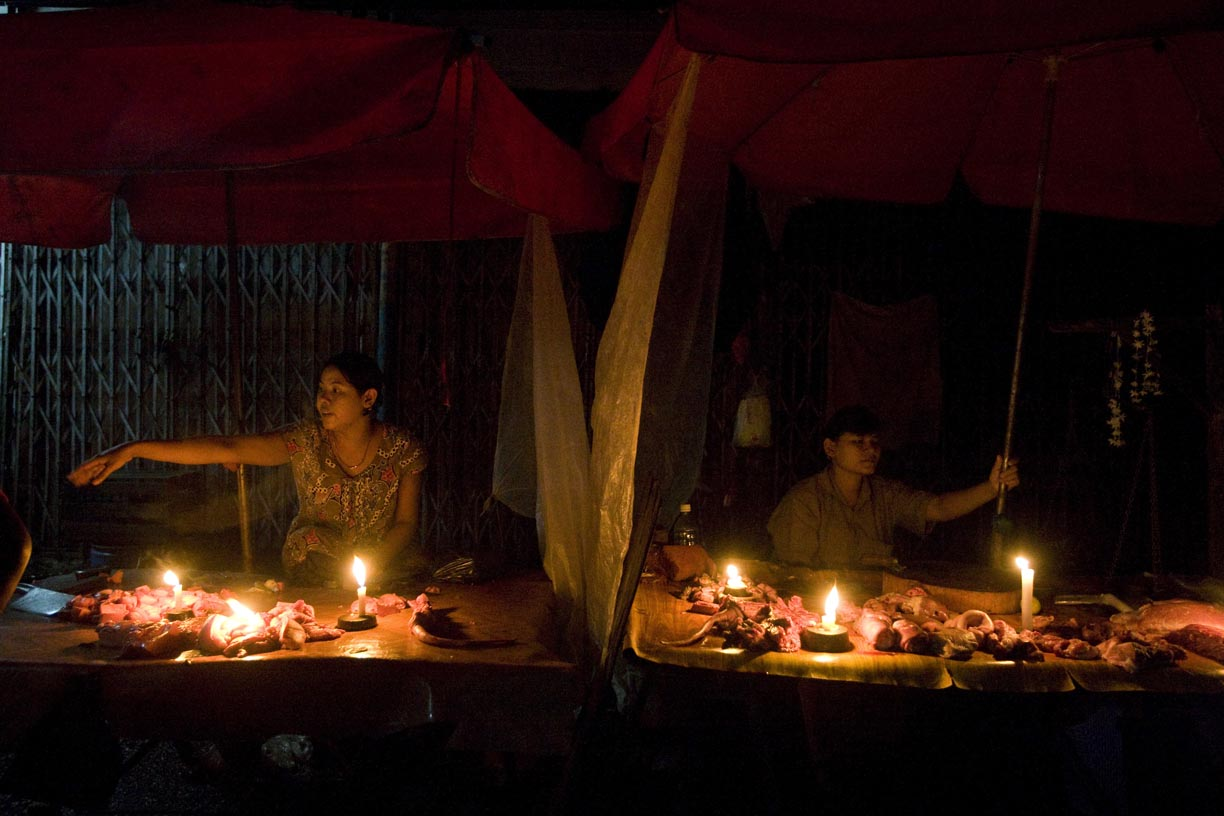 Candles provide light for vendors selling raw meat at Theingyi market.