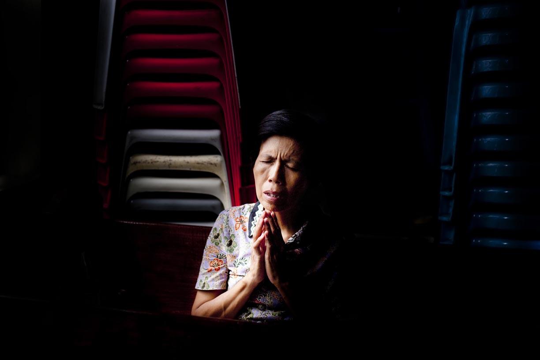 A woman prays at a church.