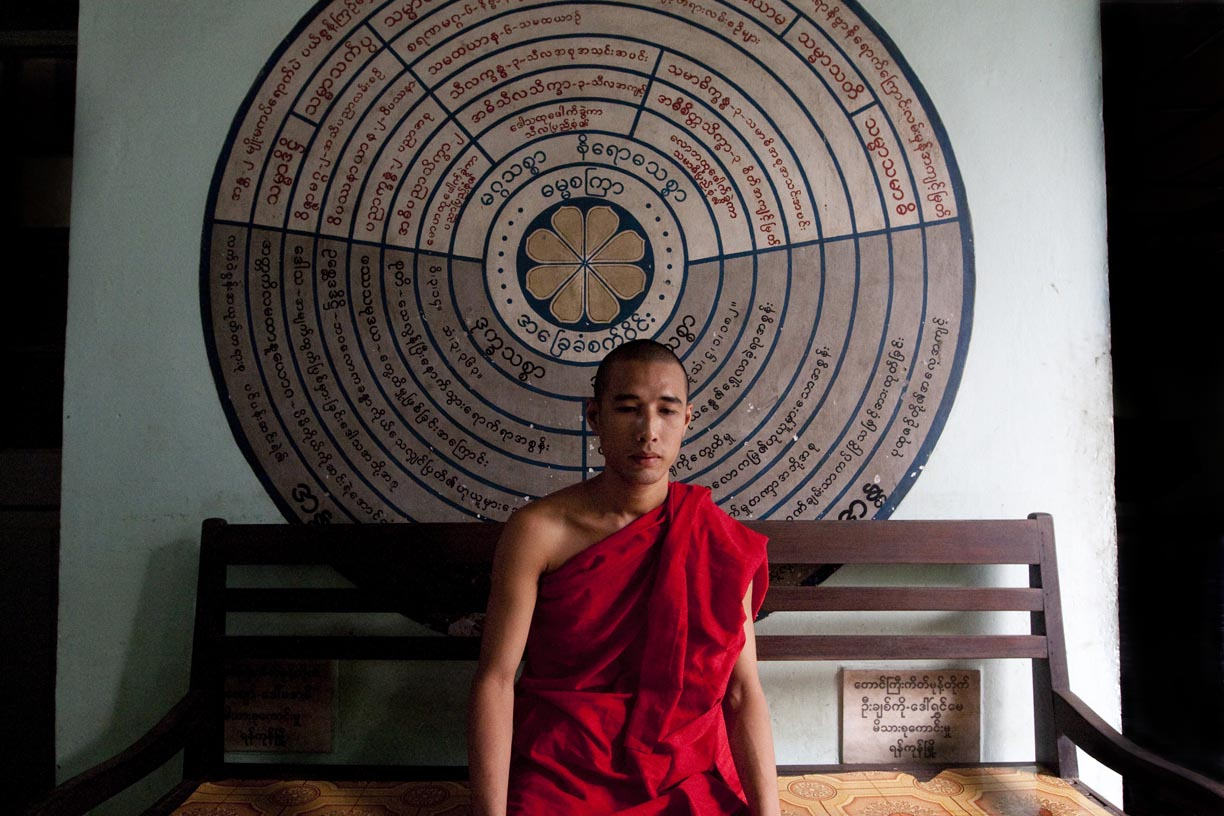 A monk poses for a photo at a temple.