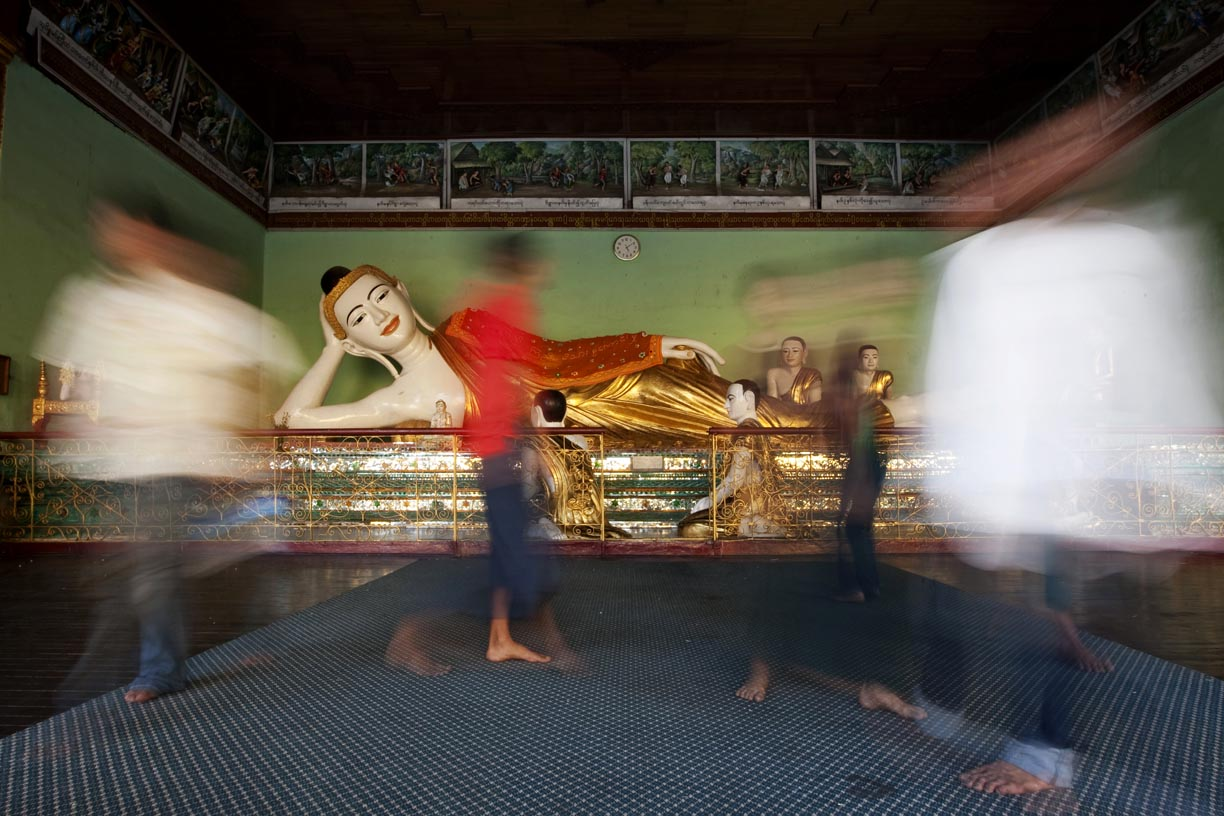 Visitors pass a lying Buddha at Shwedagon Pagoda.