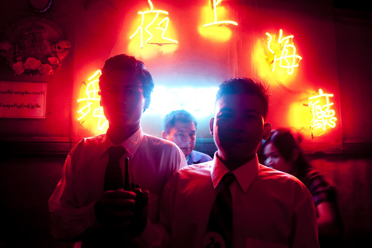 Security guards stand outside of a brothel in China town.
