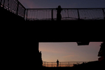 Men stand on a pedestrian overpass at dusk.