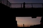 Men stand on a pedestrian overpass at dusk.