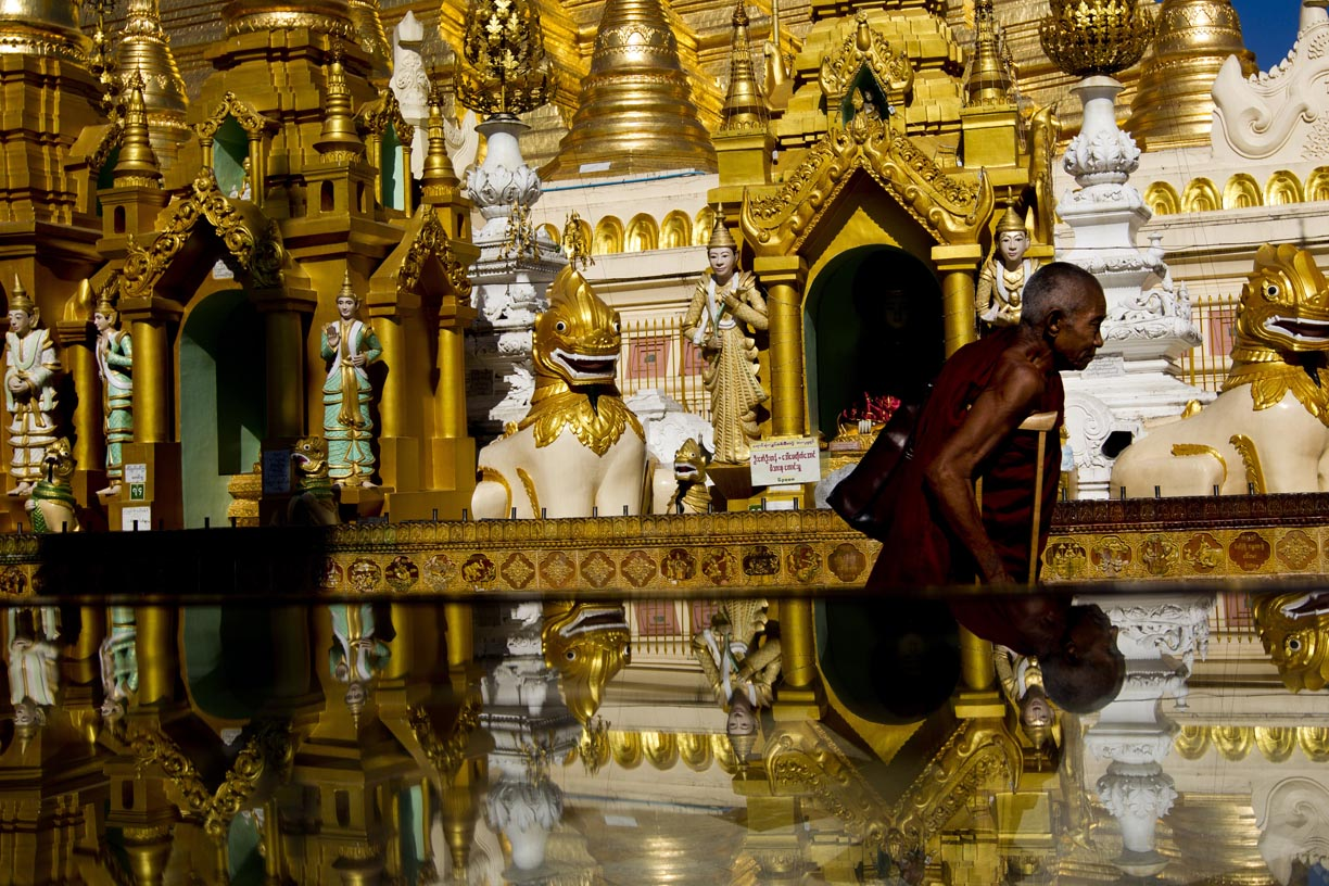 A Buddhist monk walks past the Shwedagon Pagoda.