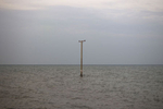 As a consequence of rising sea levels, an electrical power line pole stands in the sea where a village once stood near Wat Khun Samut Chin, Thailand.